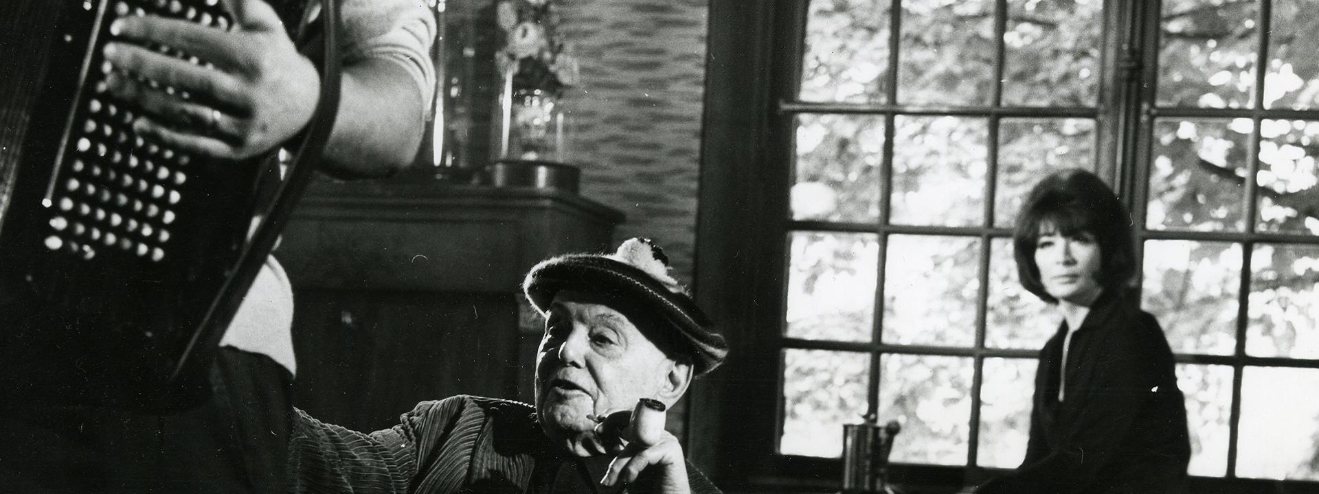 Juliette Gréco et Pierre Mac Orlan, dans la maison de l'écrivain à Saint Cyr-sur-Morin. Au premier plan un accordéoniste dont ne voit qu'un bras et une partie de l'accordéon