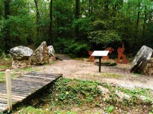 Photographie en couleur réalisée au Bois de la Barre à la Ferté-sous-Jouarre : un panneau explicatif,une meule, des pierres meulières et des silhouettes de carriers agrémentent la promenade.