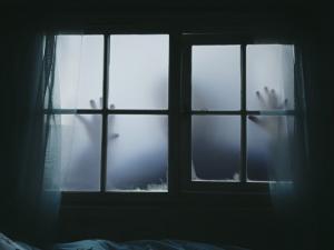 photo monochrome, deux mains et l'ombre d'une silhouette derrière une fenêtre dans l'obscurité