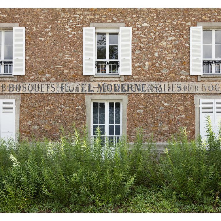 Photographie du musée, une partie de la façade ancienne en pierre meulière, avec une plantation d'osier devant. la