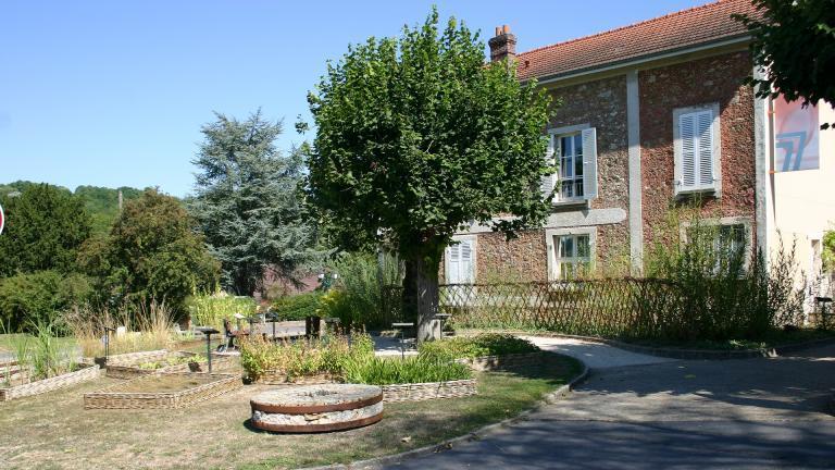 Meule en pierre, carrés de plantes utiles, tilleuls et barrière en osier devant l'entrée de la cour du Musée de la Seine-et-Marne.