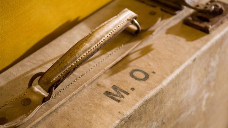 Gros plan de la poignée et des initiales M.O. sur une valise adossée à un mur jaune