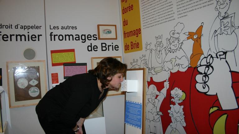 """Une visiteuse découvre les arômes des boîtes à odeurs, lors d'une visite de l'exposition temporaire """"Fromages de Brie"""""""
